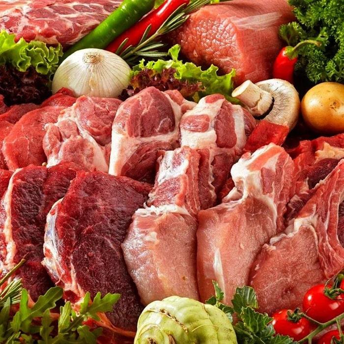 рубленные куски мяса на фоне овощей, зелени и грибов