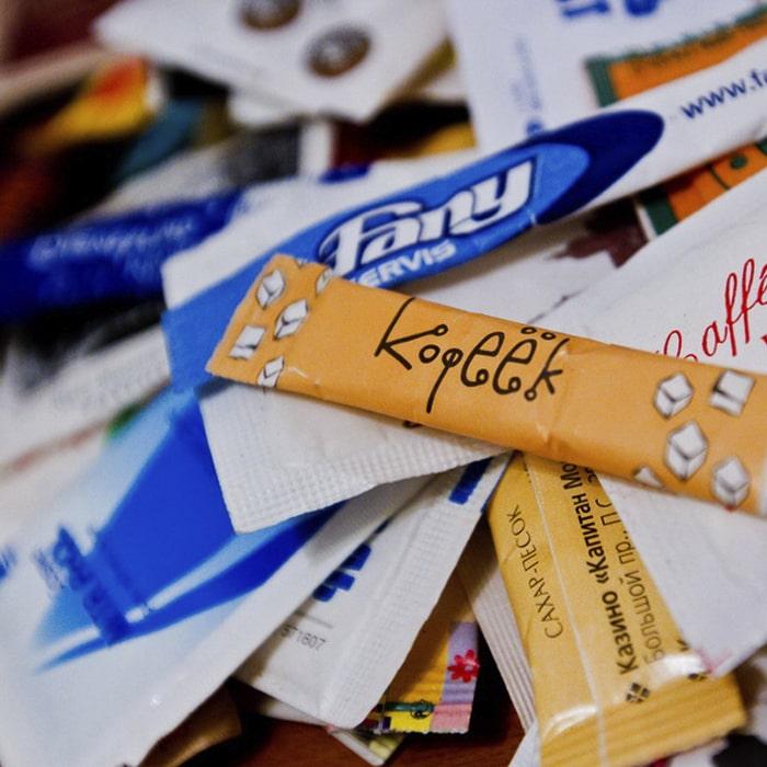 Показан ассортимент порционный сахар в стиках с логотипом.