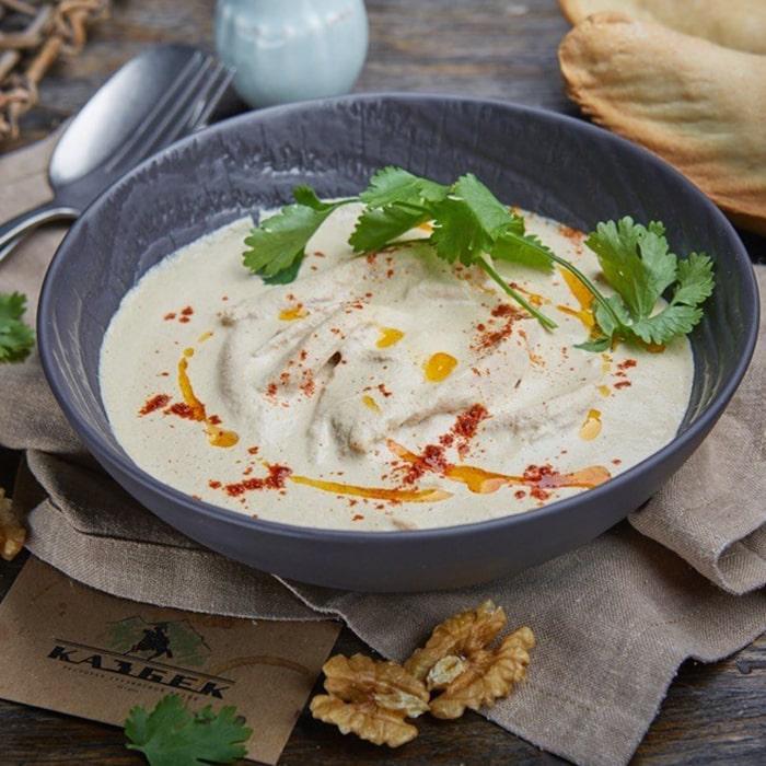 глубокая сарая тарелка с блюдом белого цвета и веточкой петрушки