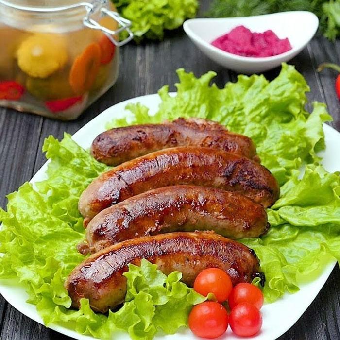 жаренные колбаски с зеленью и овощами на белой тарелке