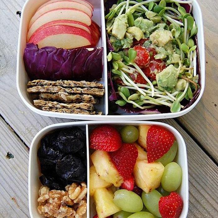 два белых контейнера, наполненные порезанными фруктами и овощами
