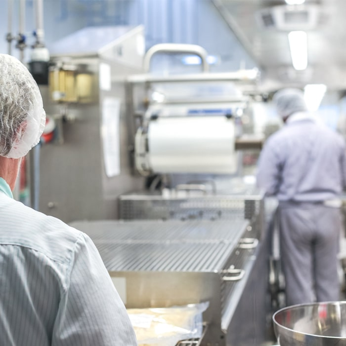 конвейер пищевого оборудования и работники в спецодежде