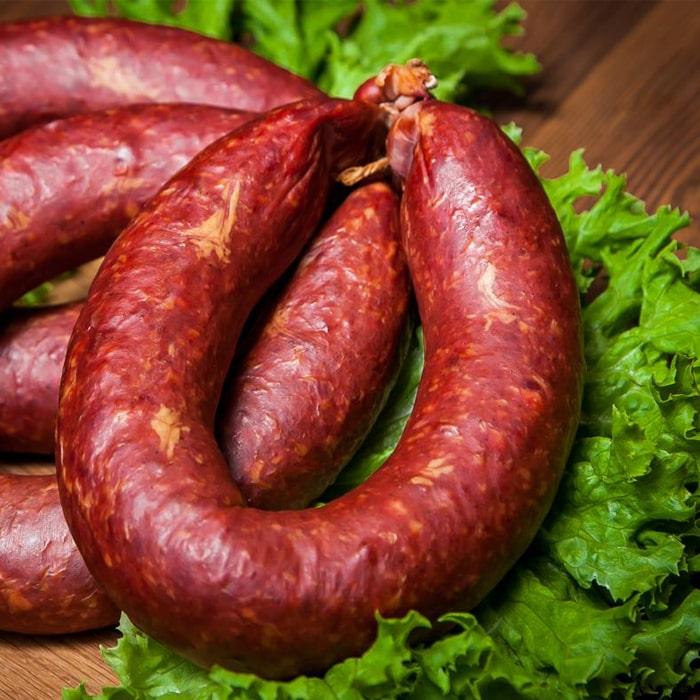 колечко полукопленой краковской колбасы на листьях салата