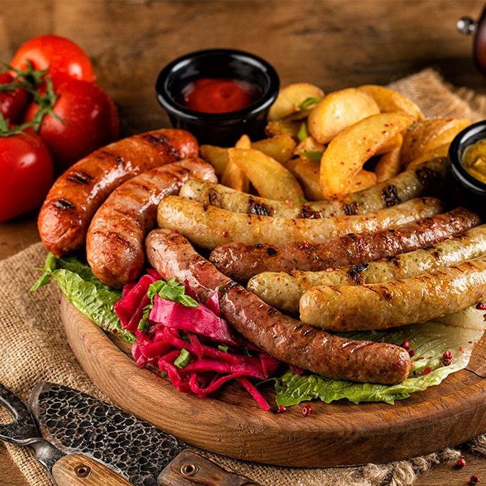 блюдо из франкфуртских колбасок с овощами и соусом