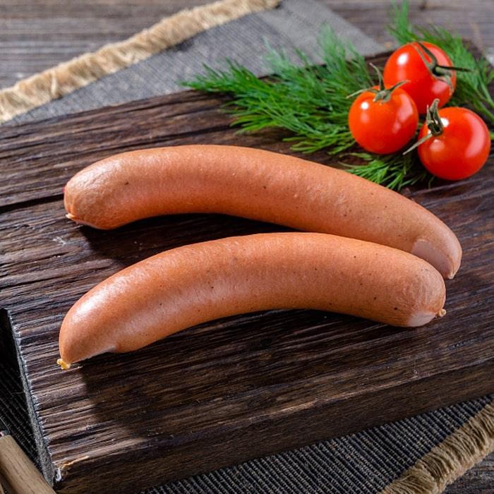 две венские сосиски на деревенном столе, зелень и овощи