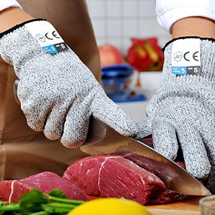 человек в защитные перчатках нарезает ножом мясо